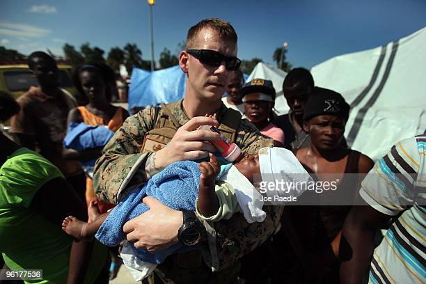 Marine Gunnery Sgt. Matt Thorp of the 24th Marine Expeditionary Unit from Montpellier, Vermont carries a baby to a hospital after it was injured in...