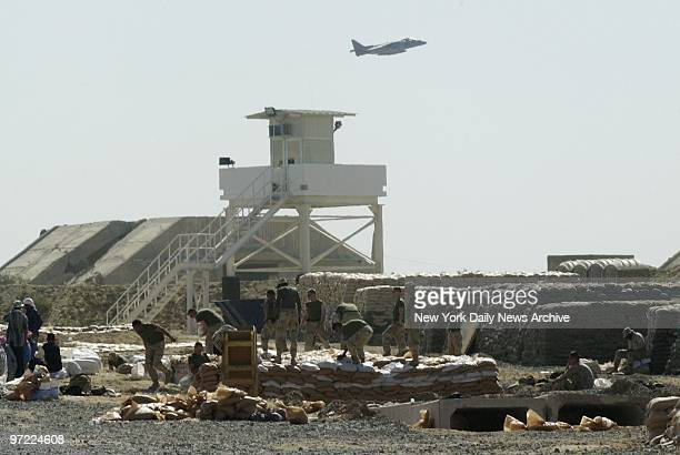 Marine Harrier jet flies overhead as US Marines build a bunker at Al Jaber Air Base in Kuwait American troops and equipment are massed in Kuwait in...