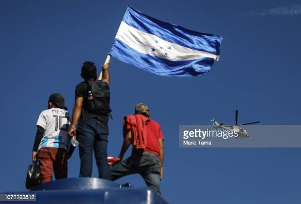 S Marine helicopter patrols above a migrant waving the Honduran flag while gathered atop a train car near the USMexico border fence on November 25...
