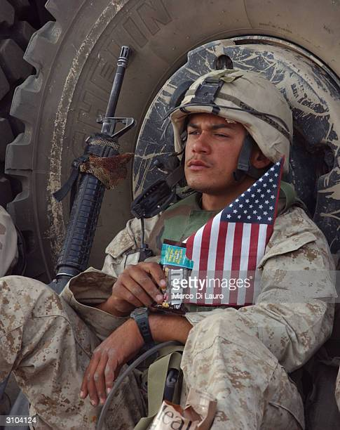 Marine holds a US flag as he rests after entering the Saddam Hussein palace April 14 2003 in Tikrit 175 kilometers north of the capital Baghdad The...