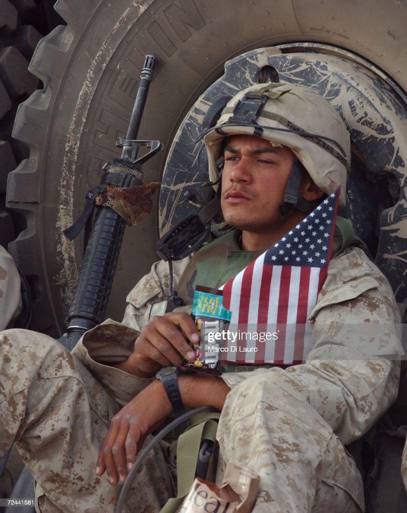 Marine holds a U.S. flag as he rests after entering the Saddam Hussein palace April 14, 2003 in Tikrit, 175 kilometers - just over 100 miles - north of the capital Baghdad. The Marines captured the city after meeting with little resistance from Saddam Hussein loyalists.