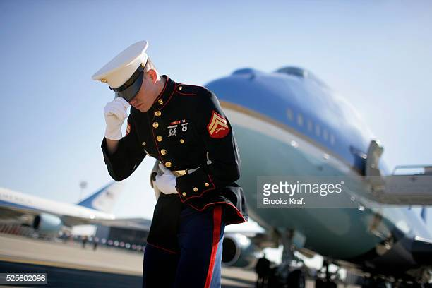 A Marine holds onto his hat as Marine One lands next to Air Force One at Ben Gurion International Airport in Tel Aviv Israel