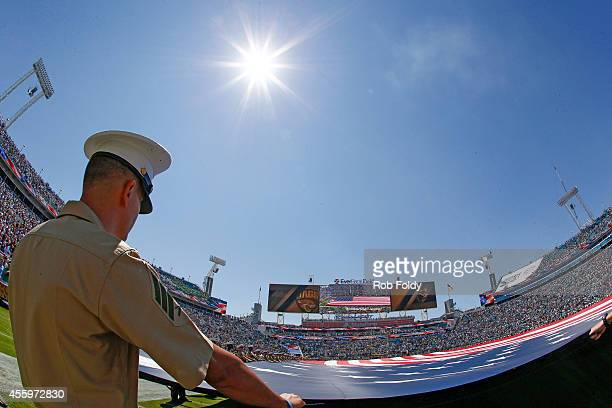 S Marine holds the American Flag during the flyover before the game between the Jacksonville Jaguars and the Indianapolis Colts at EverBank Field on...