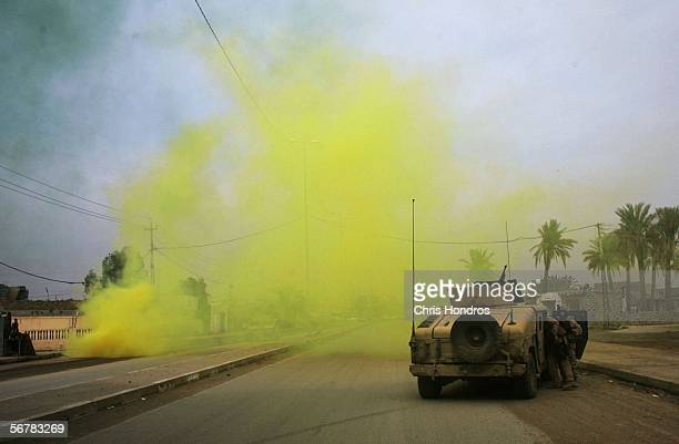 Marine Humvee is screened by yellow smoke from a smoke grenade as it stands guard during snap vehicle checks on February 8 2006 in Ramadi Iraq...