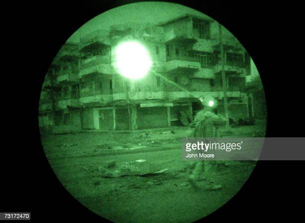 A US Marine illuminates a building using an infrared laser only visible using night vision goggles while on a search operation for insurgents in the...
