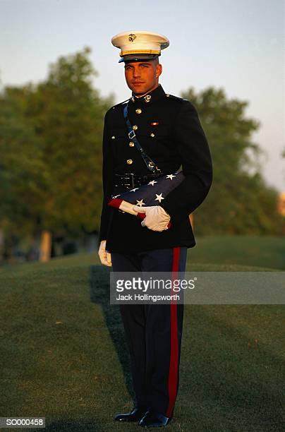 US Marine in dress uniform holding folded US flag