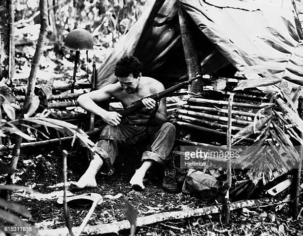 Marine in tropical dwelling, Guadalcanal, Solomon Island. | Location: Guadalcanal Island, Solomon Islands.