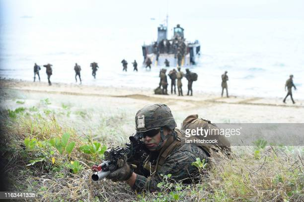 Marine is seen as troops disembark from landing craft in the background on July 22, 2019 in Bowen, Australia. Exercise Talisman Sabre 2019 is the...