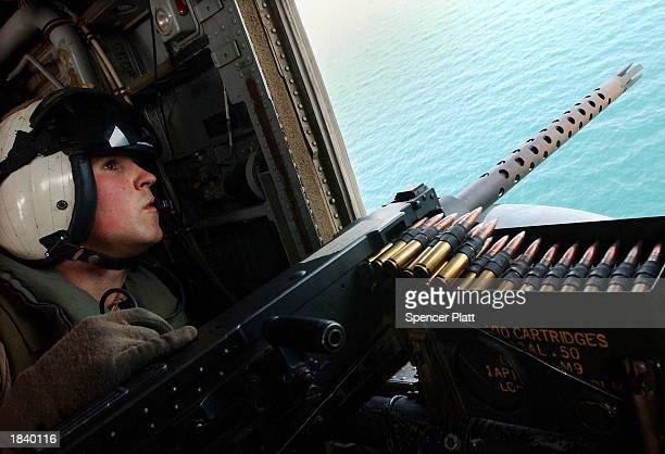 Marine keeps watch out of a helicopter before landing on the USS Bataan flight deck March 10, 2003 in the Persian Gulf. The Bataan, a multi-purpose...