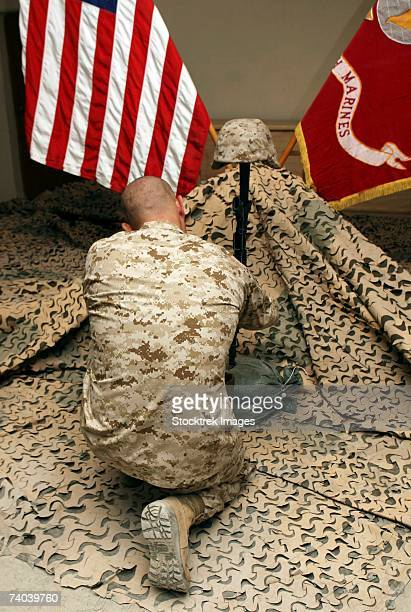 a marine kneels before the rifle, boots and identification tags during a memorial service at the habbaniyah chapel july 7. - boots rifle helmet stock pictures, royalty-free photos & images