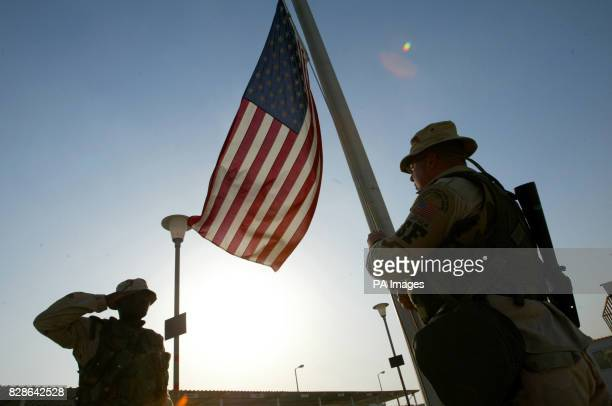 US Marine Lance Corporal Fritz Francois salutes as US Air Force Staff Sergeant Dave Buckheister lowers the US flag at their base in Kuwait Aircraft...