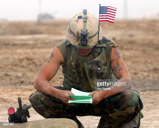 Marine Lance Corporal Stephen Plumer from Arvada, Colorado of Task Force Tarawa reads a letter from his mother March 30, 2003 in the southern Iraqi...