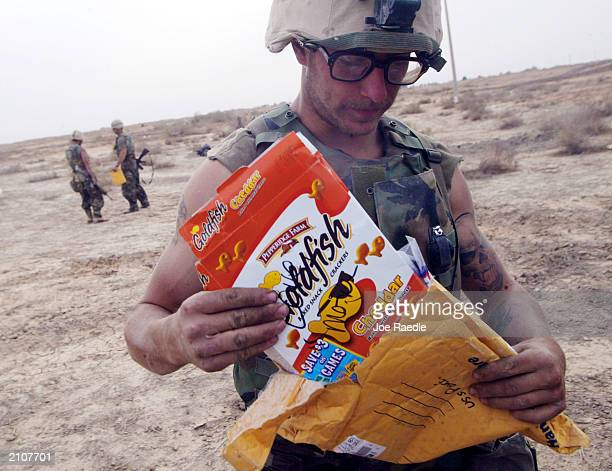 Marine Lance Corporal Stephen Plumer from Arvada, Colorado of Task Force Tarawa opens mail from his mother March 30, 2003 in the southern Iraqi city...