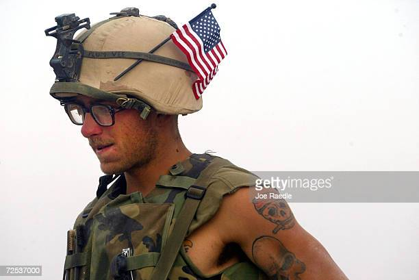 Marine Lance Corporal Stephen Plumer from Arvada, Colorado of Task Force Tarawa wears a U.S. Flag in his helmet after receiving it from his mother in...