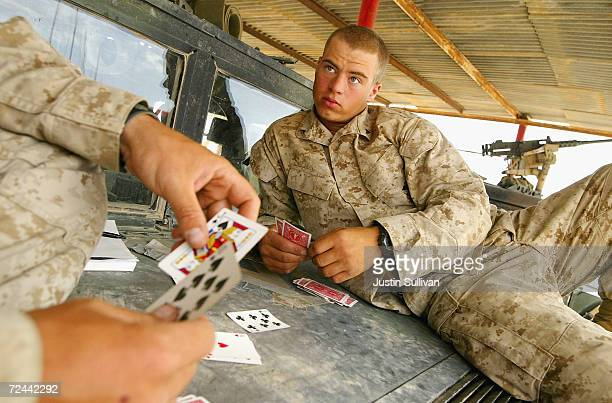 S Marine Lance Corporal Timothy Winters and Lance Corporal Jake Bond from the 2nd Battalion 7th Marines play cards on the hood of a Humvee on May 19...