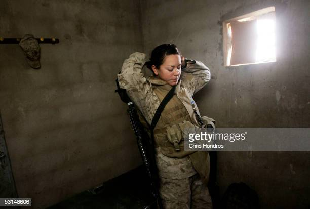 Marine Lance Cpl Jillian Masmela of Boston Massachusetts suits up for a shift as female searcher at Entry Control Point 1 a guarded entry into the...