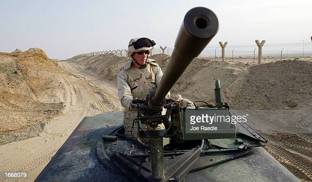 Marine Lance Cpl. Justin Dougall from South Bend, Indiana mans a .50 caliber machine gun as he patrols the perimeter in a humvee December 2, 2002 at...