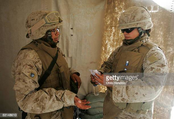 Marine Lance Cpl Olivia Watkins chats with Lance Cpl Jillian Masmela in the shed used to search female Iraqi women at Entry Control Point 1 a guarded...