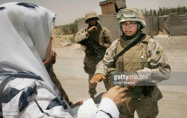 Marine Lance Cpl Olivia Watkins tells an Iraqi woman her photocopied ID cannot giver her access at Entry Control Point 1 a guarded entry into the...