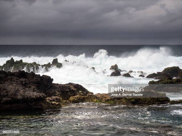 Marine landscape with sky of storm, impact of the waves on the volcanic rocks of the coast in Terceira Island in the Azores islands, Portugal.