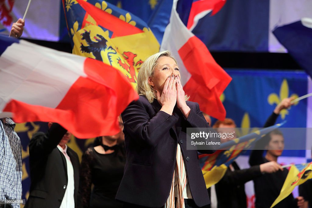 Marine Le Pen, leader of the French far-right National Front (FN) party, waves to supporters during her campaign rally for the upcoming regional elections in the Nord-Pas de Calais-Picardie, on November 30, 2015 in Lille, France.