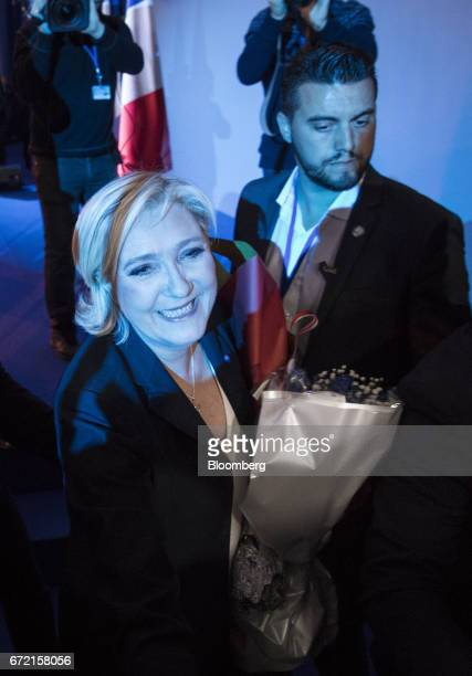 Marine Le Pen leader of the French National Front and France's presidential candidate holds a bouquet of flowers as she departs after speaking to...