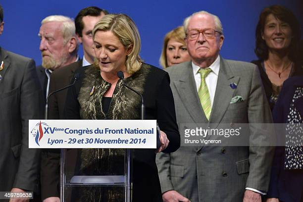 Marine Le Pen speaks from the podium as her father and party chief predecessor Jean Marie Le Pen looks on from behind at the farright National...