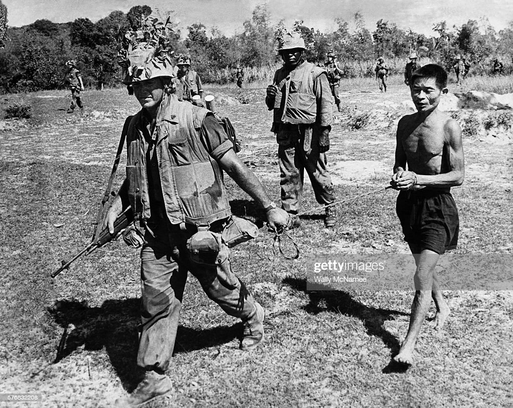 Marine leads a Vietcong suspect during a Battalion operation. The soldier carries what appears to be a M-14 and sweats through his flak jacket and trousers in this humid climate.