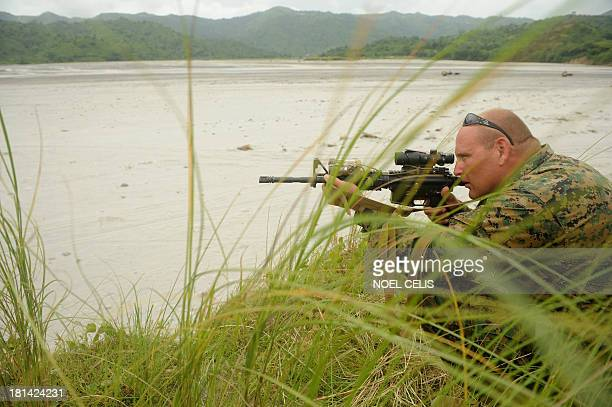 A US marine looks through the scope of his rifle among grass stalks during a military exercise at the Crow Valley Tarlac north of Manila on September...