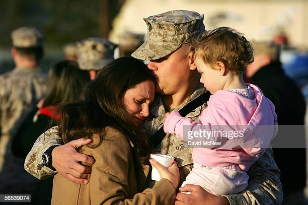 Marine Lt Bradley Schob holds his two-year-old daughter Hanna and kisses his wife Courtney as members of 3rd Battalion, 5th Marine Regiment leave on...