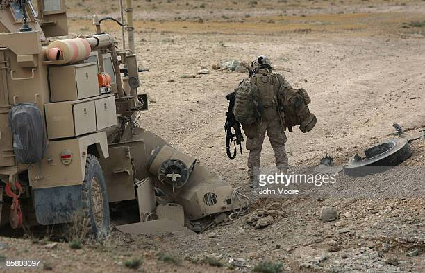 S Marine machine gunner Sgt Israel Sanchez from Dallas Tx carries his gear away after his MRAP armored vehicle ran over a Taliban roadside bomb on...
