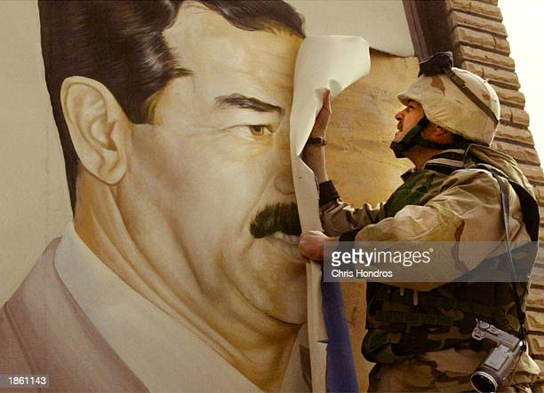 US Marine Major Bull Gurfein pulls down a poster of Iraqi President Saddam Hussein March 21 2003 in Safwan Iraq Chaos reigned in southern Iraq as...
