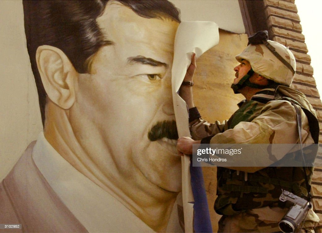 U.S. Marine Major Bull Gurfein pulls down a poster of Iraqi President Saddam Hussein March 21, 2003 in Safwan, Iraq. Chaos reigns in southern Iraq as coalition troops continued their offensive to remove Iraq's leader from power.