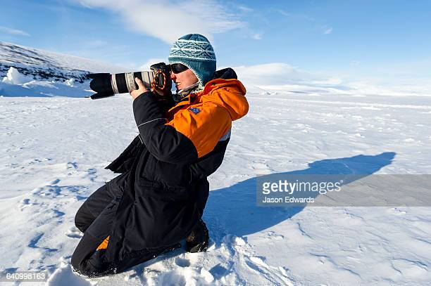 A marine mammal researcher photographing a Weddell Seal on the sea ice.