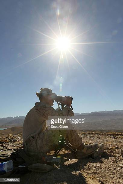S Marine marksman spotter Cpl Cody Scholes of Belfast NY with India Battery 3rd Battalion 12th Marine Regiment watches for enemy movement as he and a...