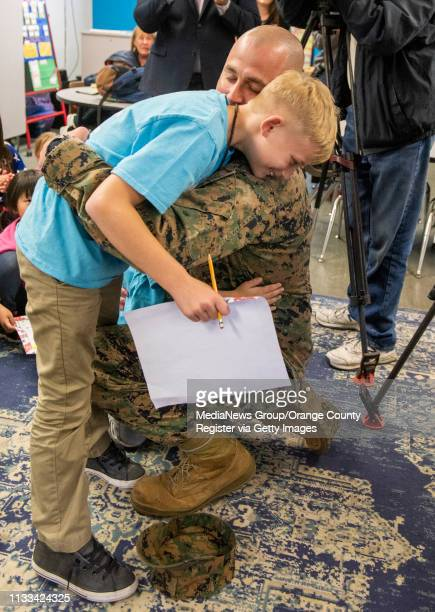 Marine Master Sgt. Jeremy Nieznanski embraces his son Hayden after he made a surprise appearance the the YMCA after-school program to surprise his...