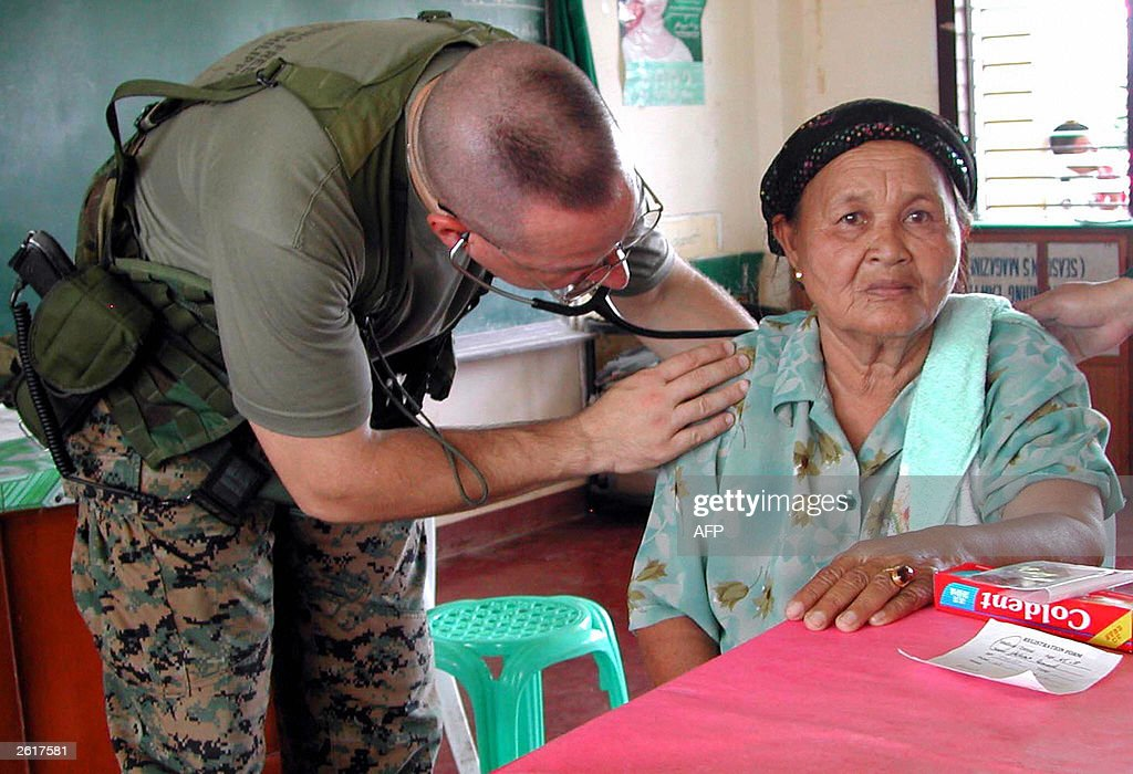 marine medic examines an elderly muslim woman as a team of us and