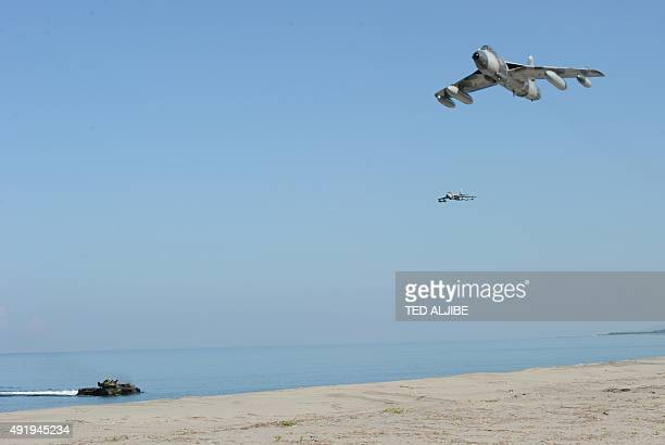 US Marine MK58 Hawker Hunter fighter jets fly over an assault amphibious vehicle during an amphibious landing exercise as part of annual joint...