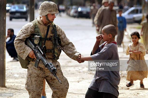 S Marine Nicholas Wahle of Alton Il shakes hands with an Iraqi boy while on a street patrol April 18 2003 in Baghdad Iraq Although the US military...