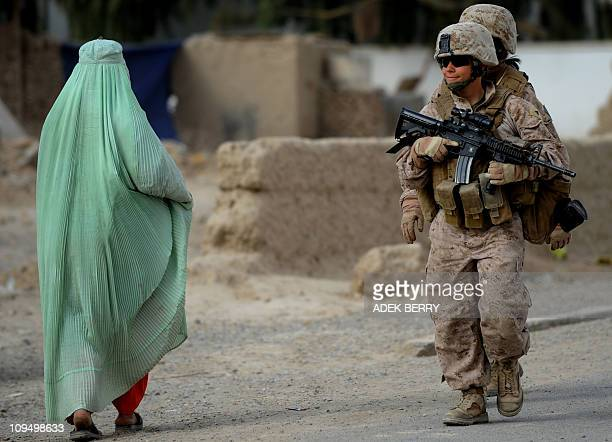 US Marine of the 2nd Batallion 1st Marines with Female Engagement Team Corporal Ashley A Cardona walks next to a burqa clad Afghan villager during a...