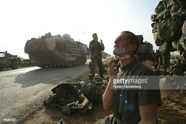 Marine of the 3rd Battalion of the 1st Marine Division shaves by the side of the highway, 60 kms south of Baghdad, April 4, 2003 as the battalion...