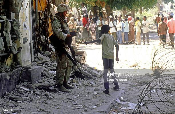 Marine on patrol speaks to a child March 3, 1993 on the streets of Mogadishu, Somalia. The U.S. Has been the main pillar in an international...