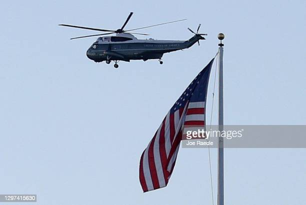 Marine One carrying President Donald Trump and first lady Melania Trump as they departed from the White House flies by an American flag ahead of the...