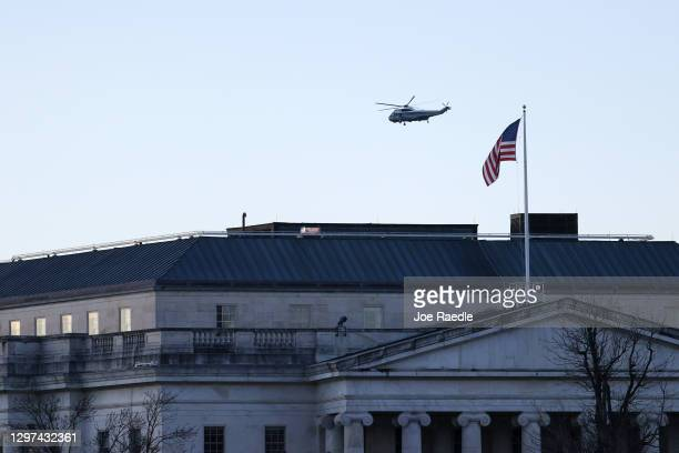 Marine One carrying President Donald Trump and first lady Melania Trump as they departed from the White House flies over the House Office buildings...