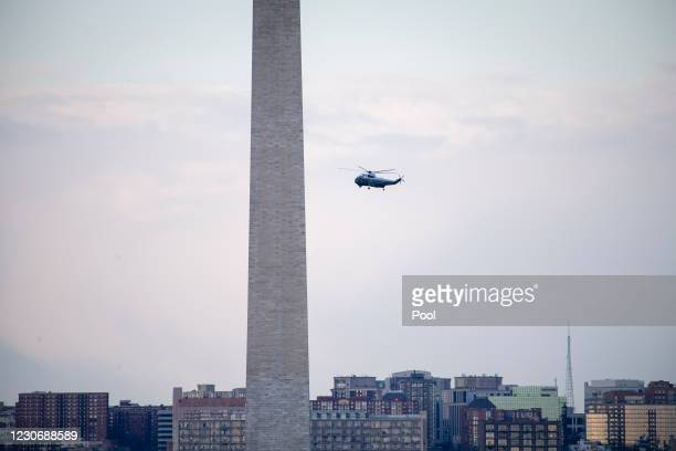 Marine One, carrying President Donald Trump, flies by the Washington Monument as it departs from the White House prior to the 59th inaugural ceremony...