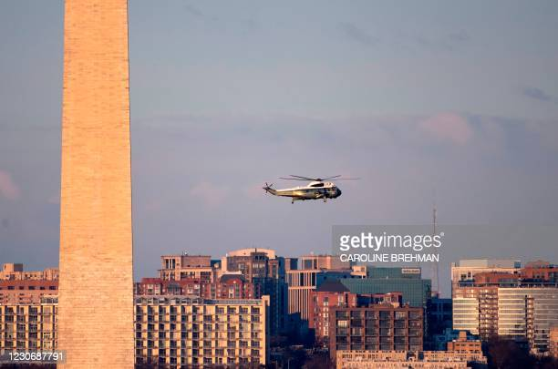 Marine One flies by the Washington Monument on its way to the White House in Washington, DC, on January 20 for the departure of US President Donald...