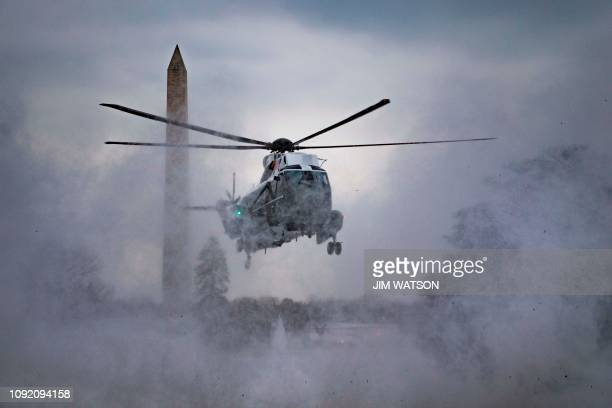 TOPSHOT Marine One kicks up snow as it lands on the South Lawn of the White House in Washington DC on February 1 2019 to convey US President Donald...