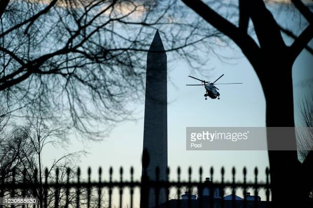 Marine One with President Donald Trump aboard flies past the Washington Monument on January 20, 2021 in Washington, DC. President Donald Trump is...