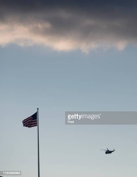 Marine One with President Donald Trump and first lady Melania Trump aboard flies past the U.S. Capitol as it departs the White House ahead of the...
