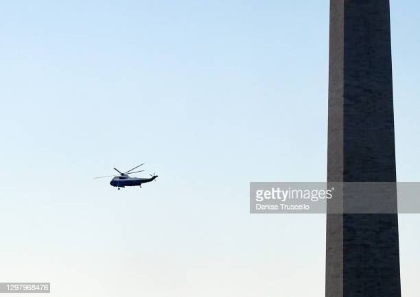 Marine One with President Donald Trump and first lady Melania Trump aboard flies past the Washington Monument as it departs the White House ahead of...